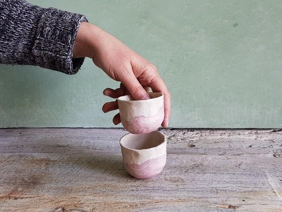 Tasse à expresso rose et blanche en poterie avec dessin de nue. Tasse avec illuminations pour le café en grès.