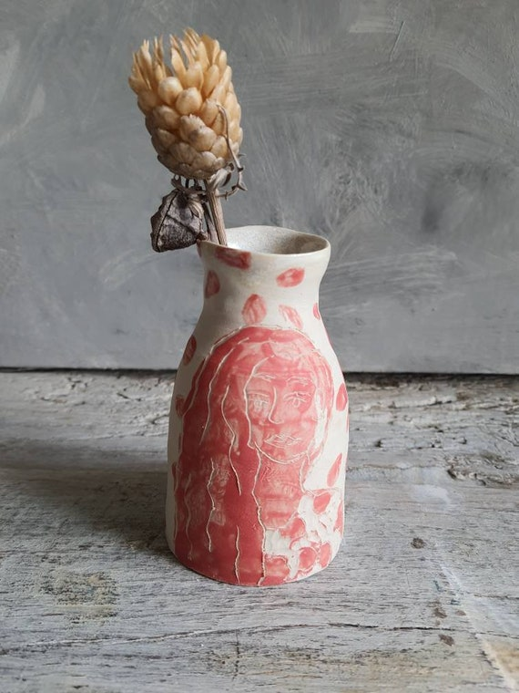 Small craft vase in pottery drawing of white woman and red ceramic sandstone