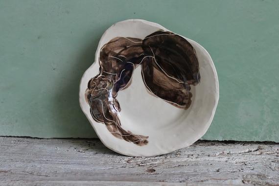 Assiette en poterie artisanale avec dessin d'artiste. Assiette en grès blanc, avec dessin de femme noire.