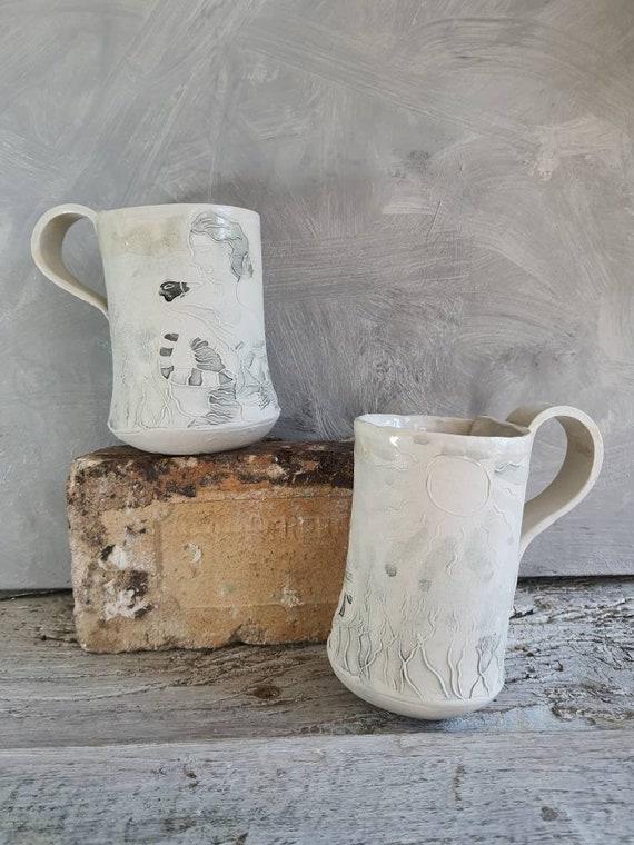 Mug en poterie artisanale . Tasse en céramique gris et blanc dessin de femme et d'oiseau. Vente en ligne de mug artisanal.