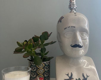 Kitsch phrenology head lamp with a tattoo and moustache design