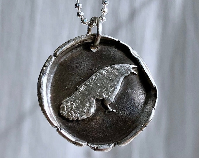 shouting crow and feather pendant