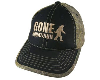 Gone Squatchin Humorous Sasquatch Bigfoot Silhouette Beige Embroidery on an Adjustable Black on Realtree Style Camouflage Style Baseball Cap