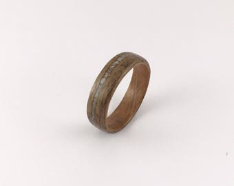 Walnut wood ring with offset white crushed glass inlay and cherry wood liner