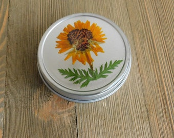 Orange flower tin with mystery set of stitch markers