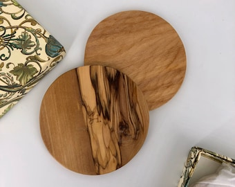 Coasters, sculpted by hand. Olive and cypress wood. A refined natural oil finish.
