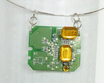 Upcycling. Green circuit board pendant and orange beads. Piece of electronics. Recycled jewelry.