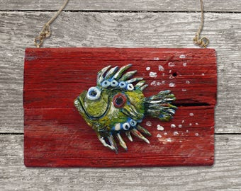 Fish relief made of plasterboard on a wooden board