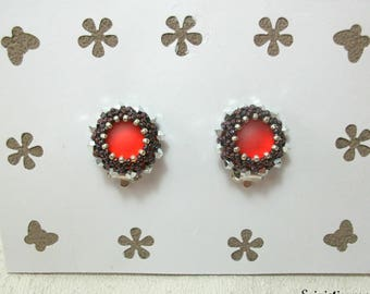 Earrings clip flat beads woven around a red cabochon