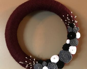 Burgundy yarn wreath with black, white and gray felt flowers