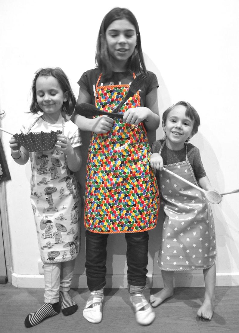 Child apron in cotton-studded peas rounds lozenges orange image 0