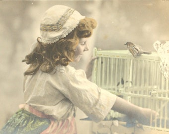 Little girl opening the cage of his bird-old postcard France - 1900 s - black and white photo sequined