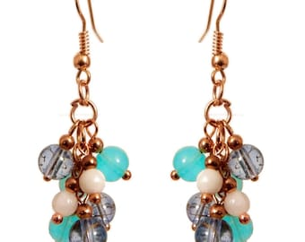 Women dangle small blue and white glass cluster earrings