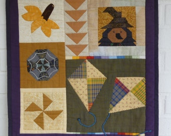 """A small Fall-Quilt with different Patterns, which belong to the Autumn like """"flying geese"""", a witch, etc."""