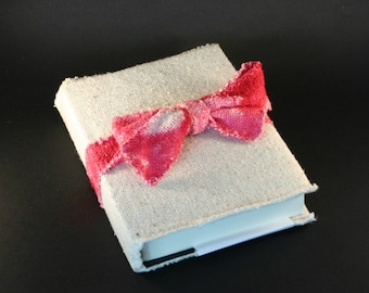 Writing book, blanket in natural silk and pink bow.