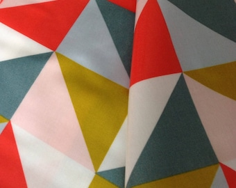 Canvas coated cotton, geometric, triangles, blue, ochre and mustard, pink and Red coral, sold a Cup by 25cm