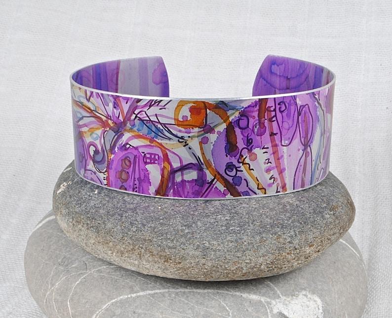 Cuff bracelet; hand painted anodised aluminium; abstract floral pattern; purple; pinks; orange; Irises; Boho; artistic.