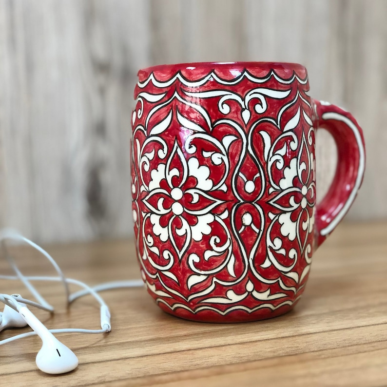 Big red ceramic mug with cotton bud ornaments. image 0