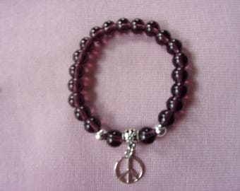 Purple glass stretch bracelet with silver peace sign charm