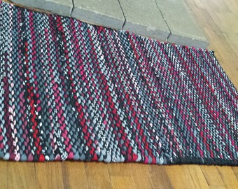Black and red twined rag rug,
