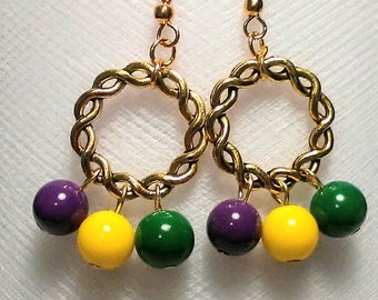 Beautiful Mardi gras glass beads in purple gold and green hung from a gold hoop earrings