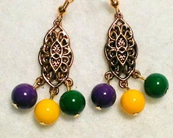 Long drop Mardi gras glass bead earrings hung from a beautiful gold bead