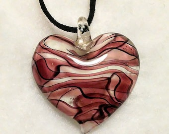 Beautiful purple and white swirl lampwork glass pendant hung on a black leather cord necklace