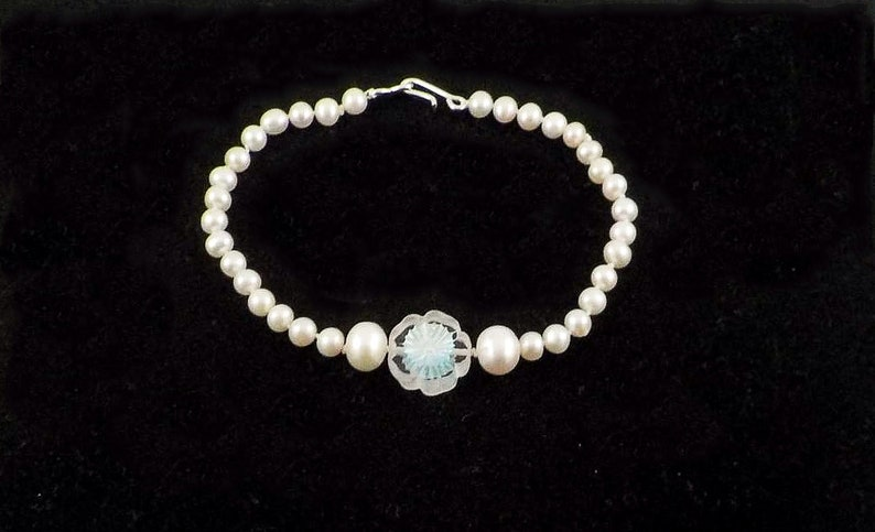 white freshwater pearls Pearl bracelet with a pearlescent Czech glass 5 petal flower central motif and a sterling silver hook eye clasp.