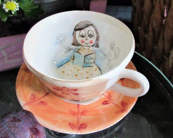Tea cup with hand made ceramic saucer with reader illustration