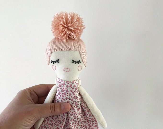 Lila fabric doll with pink hair and flower dress