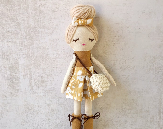 Small fabric doll in ochre tones and with accessories.