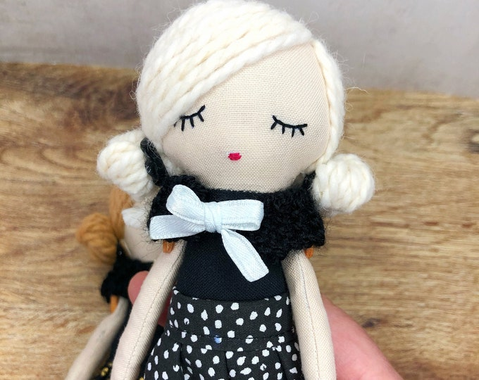 Small fabric doll with black dress.