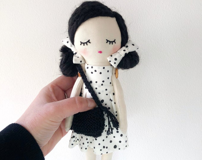 Textile doll with bag and white dress with black polka dots.