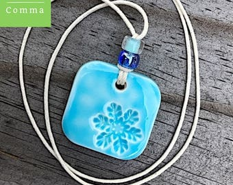 Ceramic snowflake pendant or charm, glazed light blue, handmade stamped clay necklace, winter jewelry, pottery gift, porcelain tag