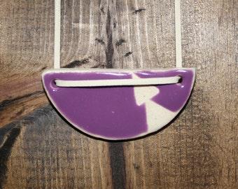 Purple ceramic pendant on faux suede cord