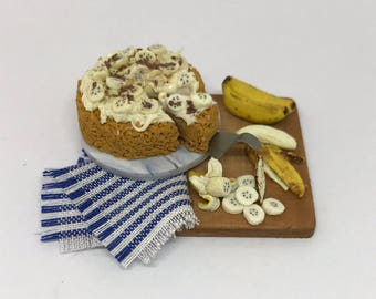 Twelfth scale handmade miniature banoffee pie and bananas on a wooden preparation board