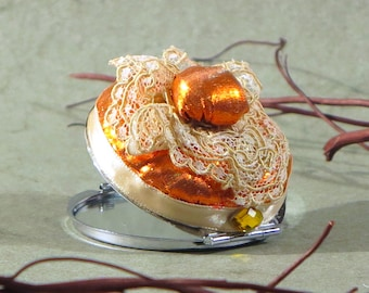 Pocket mirror with orange fabric, cream Ribbon and lace.
