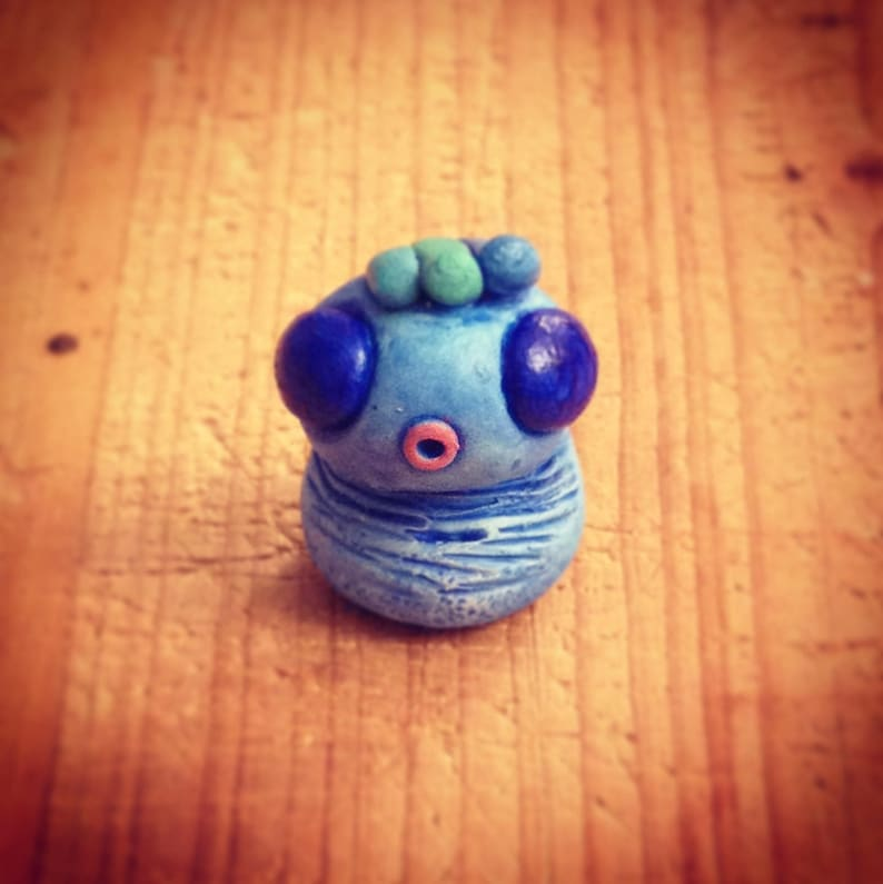 Blue Monster mini sculpture and his crest image 0