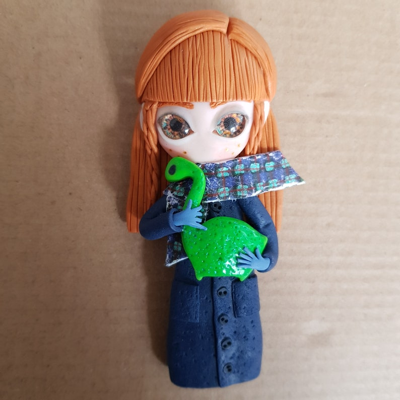 Self-portrait figure carrying a miniature Lochness monster image 0