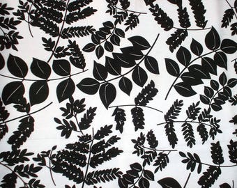 White fabric with patterns of black leaves, polyester, 110 cm width.