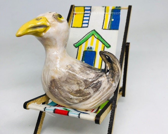 Brighton Seagull sculptures sitting on his deck chair. Handmade in Woofing Fabulous pottery studio in Sussex. Hand painted & sculpted.