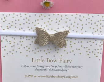Pale gold mini bow on a band