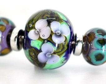 Eleven Bead Set  - Princess & Light Purple on Greens. Encased Floral Plus Eight Companion Beads