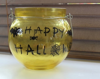 Yellow decorative glass globe-shaped bowl/lantern with 'Happy Halloween', bats, spider and spider web.