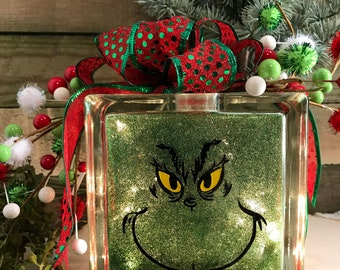 grinch glass lighted block with red and green ribbon and christmas decorations added for a unique christmas decoration for your decorating
