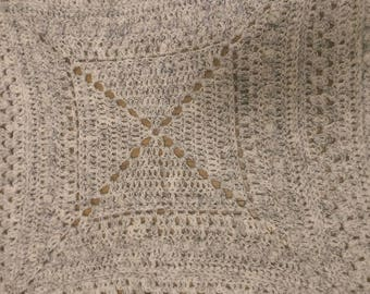 White, black speckled, intricate granny square afghan. Lacey and warm.