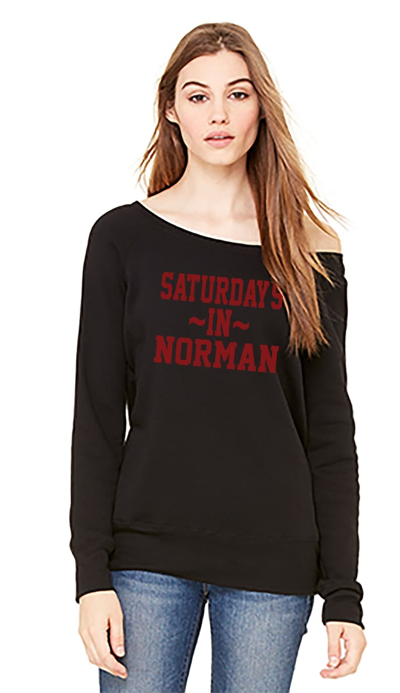 Saturdays In Norman on a classic pullover fit fleece sponge sweatshirt that can be worn pulled off the shoulder.