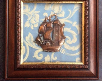Vintage frame with old fabric and copper boat