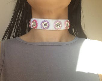 White velvet choker with different tones of pink and purple bicone beads sewn around shiny centre gems.