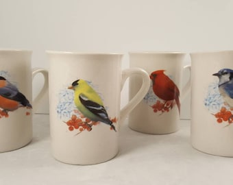 Four coffee mugs featuring song birds.